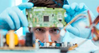 Image of Man looking at computer circuit